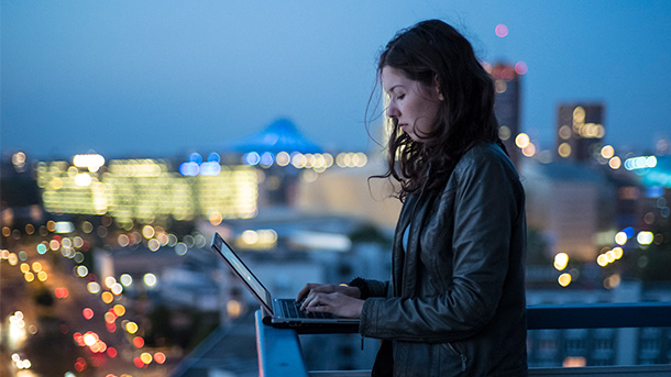 5G Solution, image of a girl holding phone in balcony with city view in background